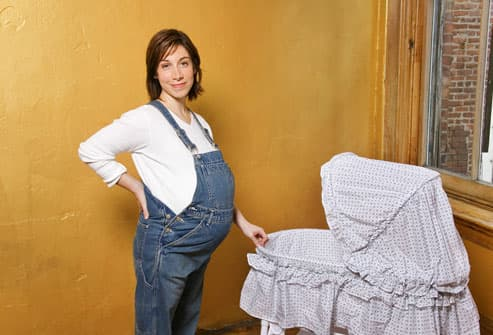 Pregnant woman with bassinet