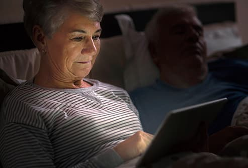 senior woman using laptop in bed