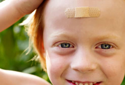 Smiling Child With Bandage on Forehead
