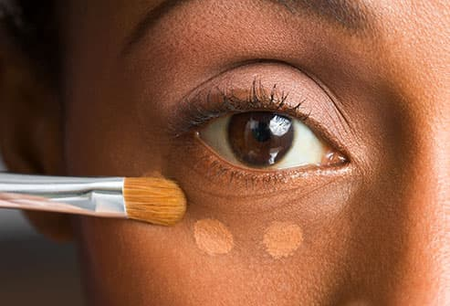 woman applying under eye concealer