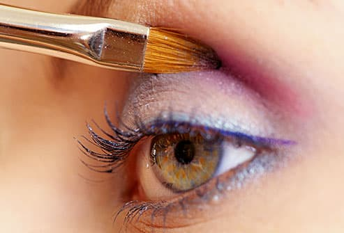 woman applying colorful eye shadow