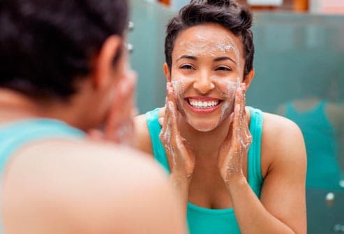 smiling woman washing her face