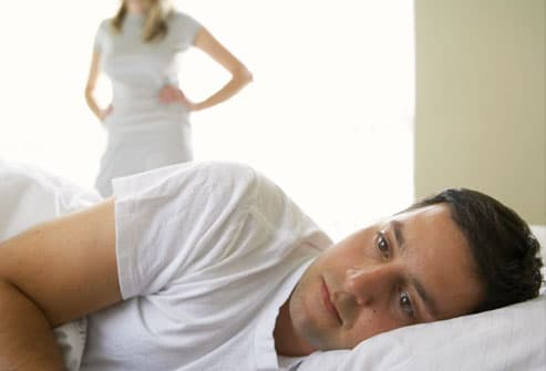 man lying in bed, woman standing in background