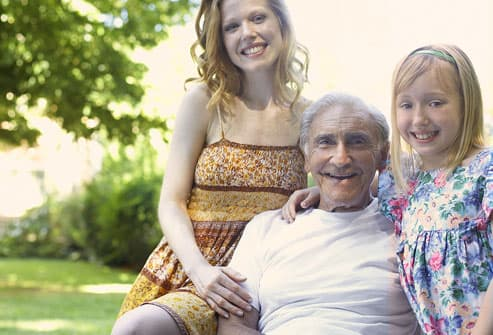 Grandfather and granddaughters smiling, portrait