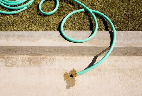 dry lawn and garden hose on kerb
