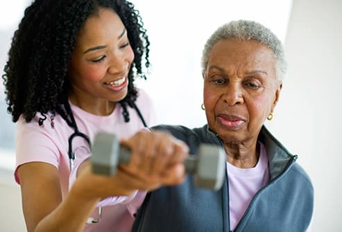physcial therapist helping woman exercise