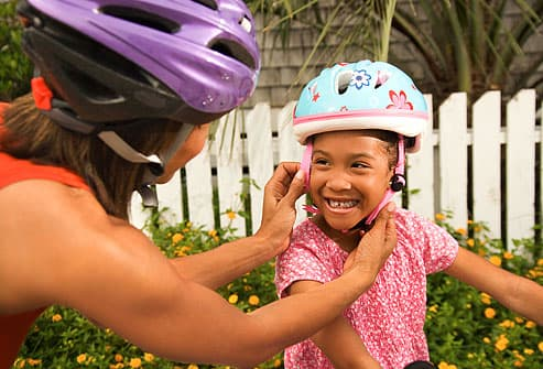 mother placing helmet onto child