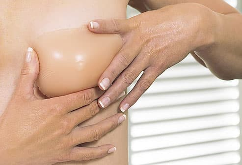 Woman Applying Breast Form