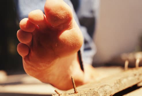 Bare Foot About to Step on Rusty Nail