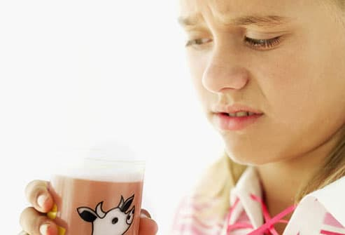 Repulsed girl with glass of chocolate milk
