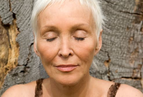 Mature woman with eyes closed leaning against tree