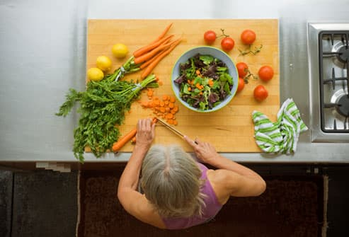 Mature woman chopping salad on cutting board