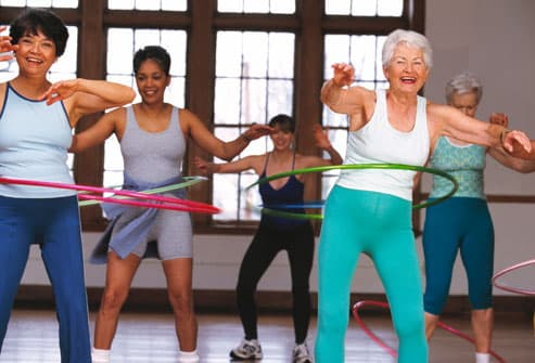 Mature women using hula hoops in exercise class