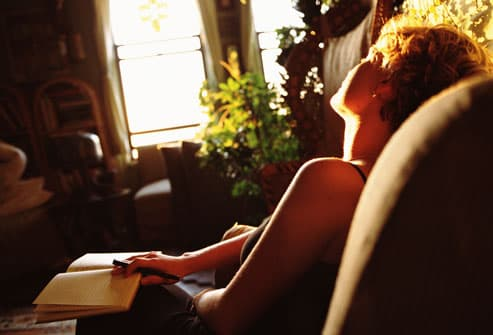 Woman writing in diary in sunlight at home