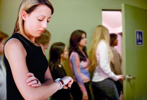 Woman checking watch in restroom line