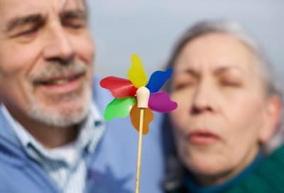 older couple blowing on pinwheel