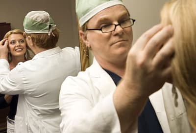 Doctor Looking at Woman's Face