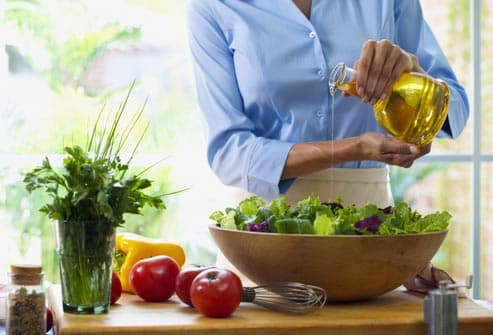woman pouring oil on salad