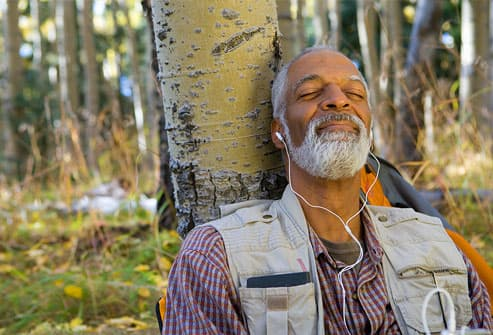 Man sitting in woods listening to music