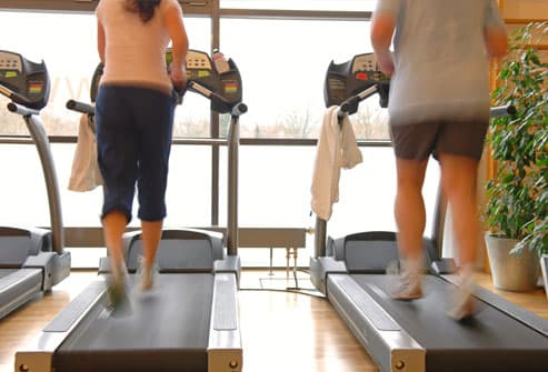 couple on a treadmill in a gym