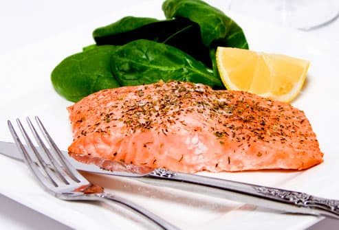 Salmon fillet with spinach and lemon wedge