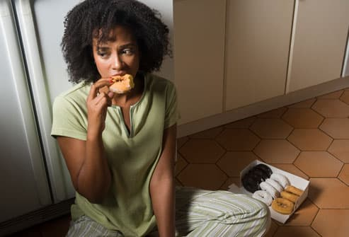 Woman binging on donuts