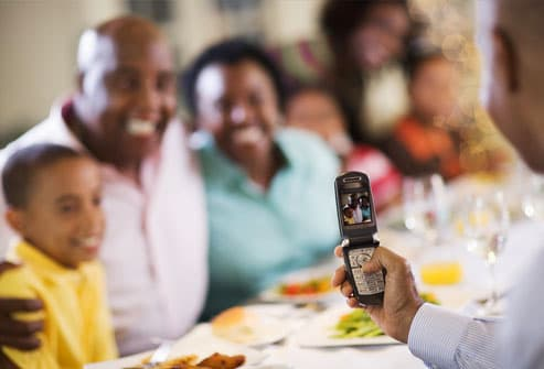 Man Taking Picture of Family on Cell Phone