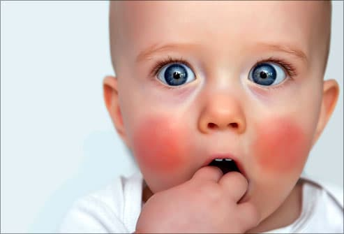 Teething baby with hand in mouth
