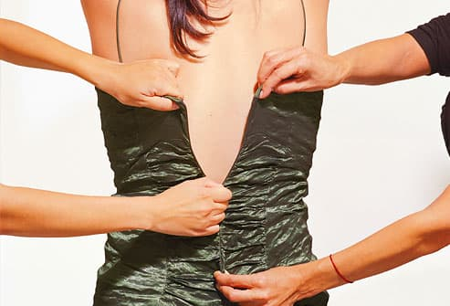 Woman being fitted into dress