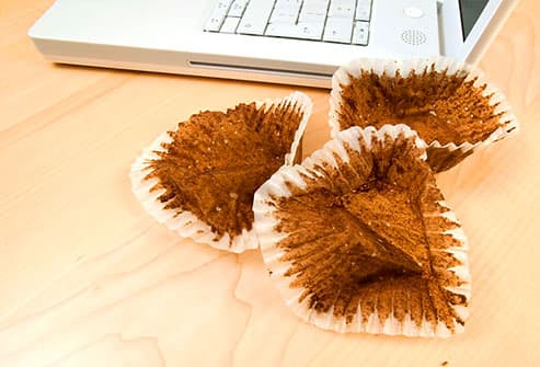 Empty cupcake wrappers beside laptop