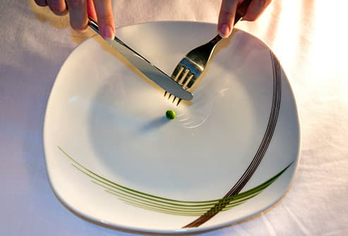 dieter with plate of one green pea