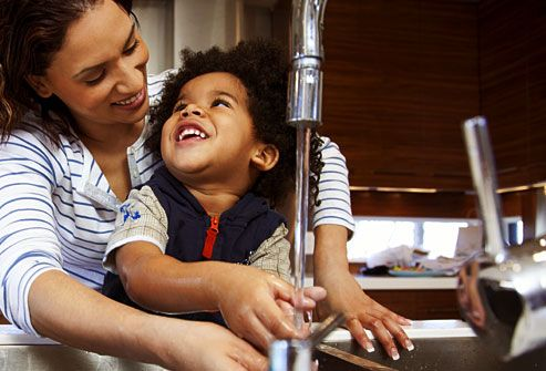 mother helping son wash hands