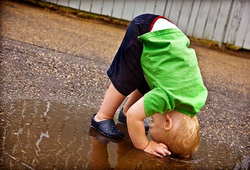 boy playing in puddle