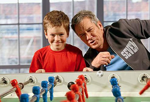 Man playing foosball with grandson