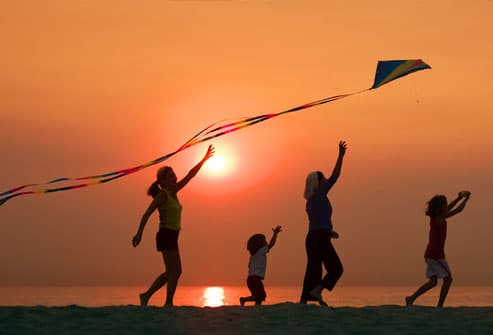 Woman flying kite with kids