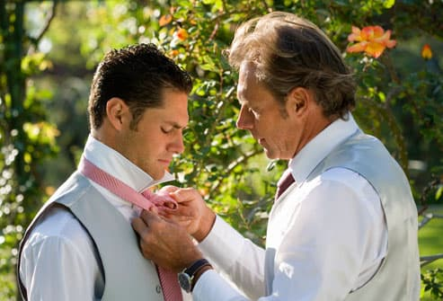 Mature father helping groom with tie in garden