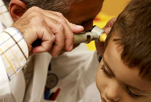 Doctor using an otoscope to examine a boy's ear