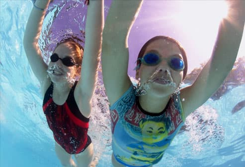 Two girls swimming underwater in pool