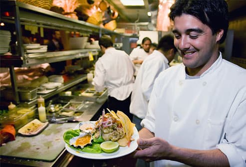 Cook holding completed entree in kitchen