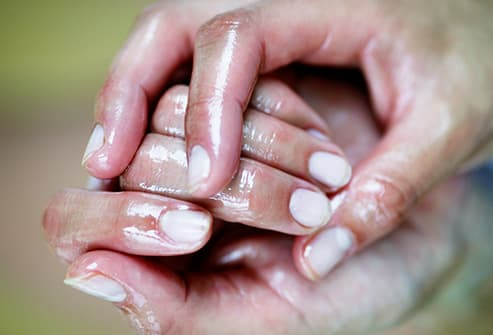 person rubbing essential oil on hands