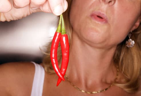 Woman holding hot peppers away from face
