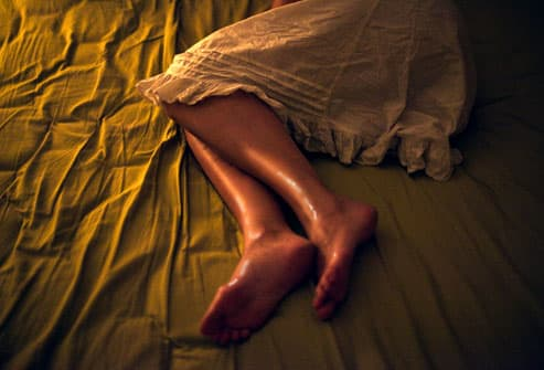 Woman experiencing night sweat in bed