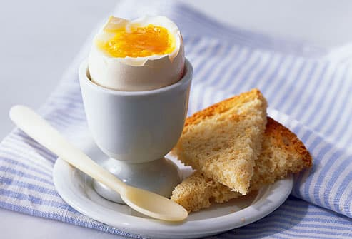 Boiled egg in cup with wheat toast