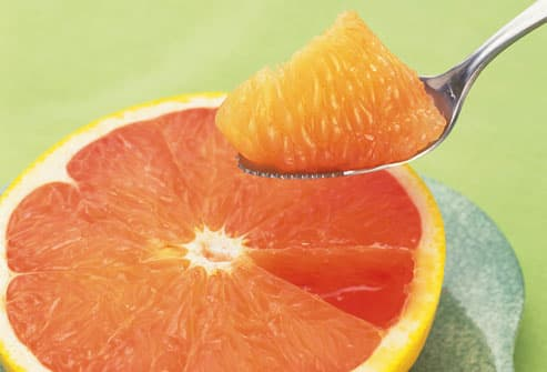 Half Of Grapefruit With Spoon