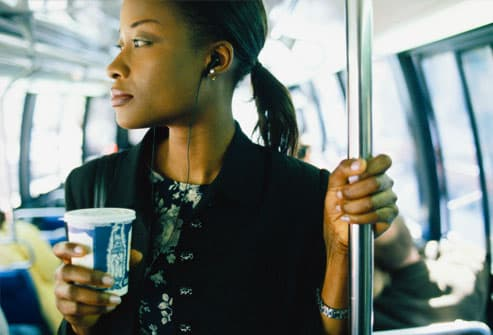 Businesswoman on bus holding cup of coffee