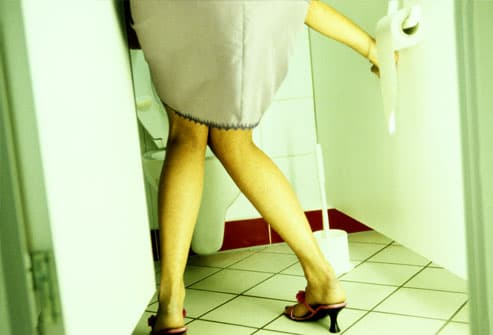 Woman entering bathroom stall, knees together