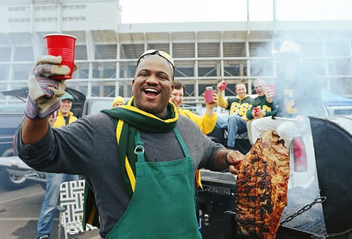 Man grilling slab of ribs at tailgate party