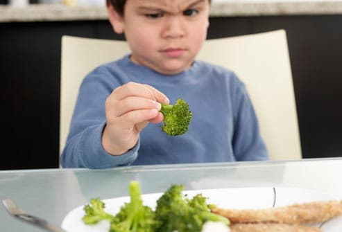 boy making face at brocolli