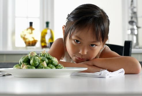 girl with plate of brussel sprouts