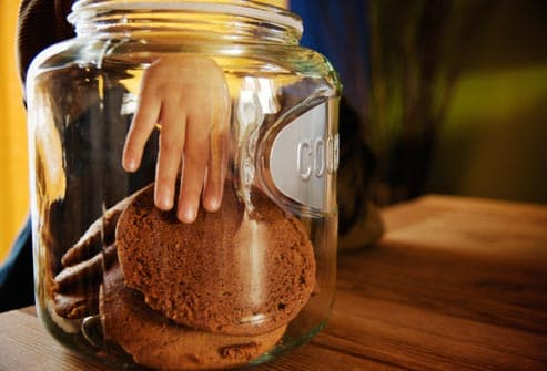child reaching in cookie jar